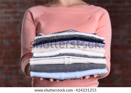 Woman hold clothes pile against brick wall background, close up - stock photo