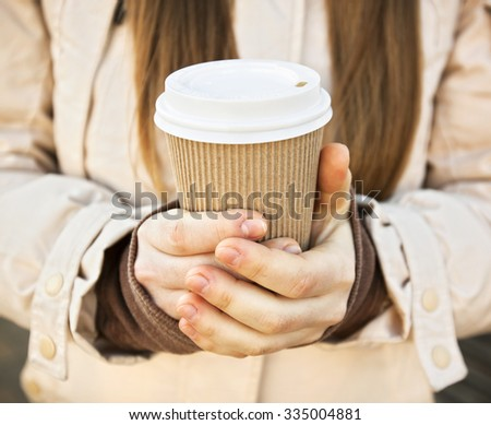 Woman hold cup of coffee on stree - stock photo