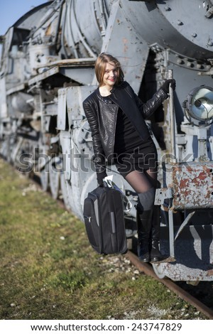 Woman hold on rusty train with left hand - stock photo