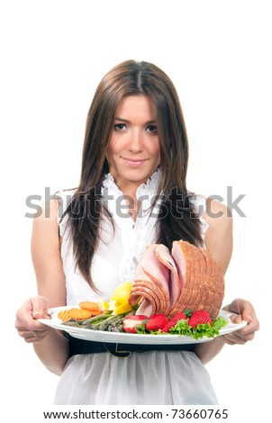 Woman hold plate delicious whole baked honey sliced ham, fresh strawberries, vegetable salad, carrots, asparagus, organic lemons for dinner isolated on a white background