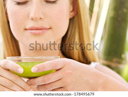 woman hold the cup of green tea - stock photo