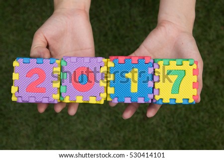 Woman hold toy puzzle wording 2017 on hand with green grass background