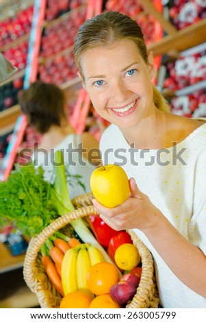 Woman holding a basket full of different fruit - stock photo