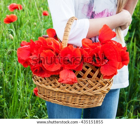 woman holding a basket with poppy flowers