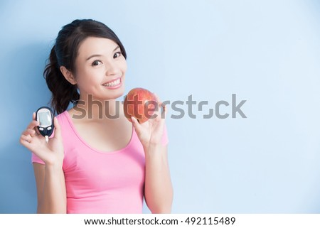 Woman holding a blood glucose meter and apple to prevention diabetes isolated on blue background, asian