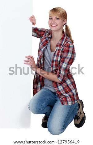 Woman holding a board left blank for your message - stock photo