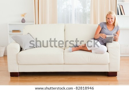 Woman holding a book in her living room - stock photo