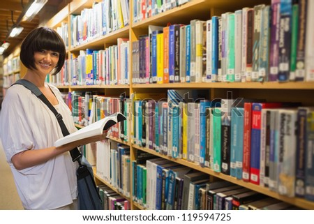 Woman holding a book next to a shelf in the library - stock photo