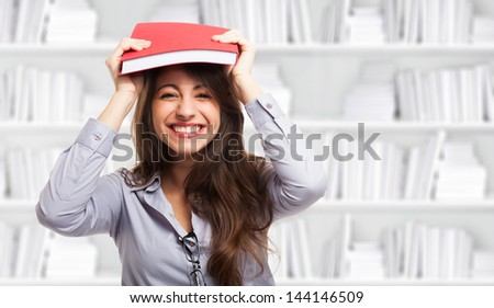 Woman holding a book over her head - stock photo