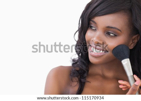 Woman holding a brush while looking against white background