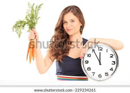 Woman holding a bunch of carrots and a big wall clock seated at a table isolated on white background - stock photo