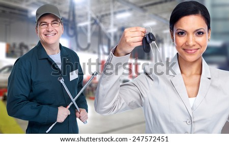 Woman holding a car key. Auto repair service - stock photo