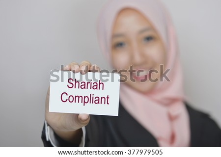 Woman holding a card with Shariah Compliant. It is banking activity that is consistent with the principles of Islamic law and its practical application through the development of Islamic economics.  - stock photo