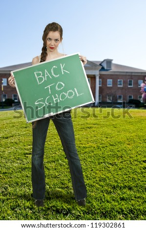 Woman holding a chalkboard that says back to school - stock photo