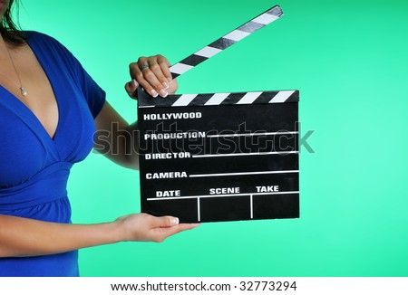woman holding a clapper board on a green screen - stock photo