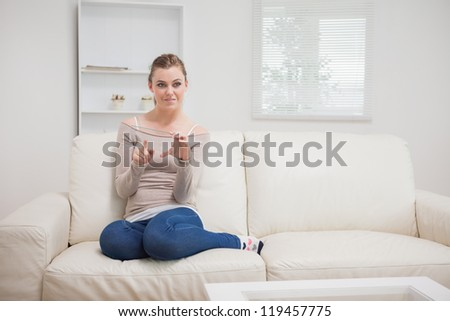 Woman holding a clear pane as a tablet pc while sitting on the sofa and smiling - stock photo