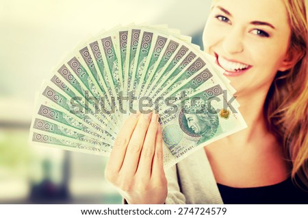 Woman holding a clip of polish money in hand - stock photo