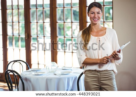 Woman holding a clipboard in a restaurant