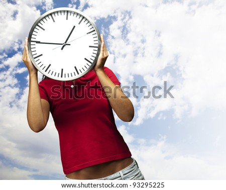 woman holding a clock in front of head against a cloudy sky background - stock photo