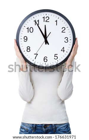 Woman holding a clock over face isolated on a white background. Time concept - stock photo