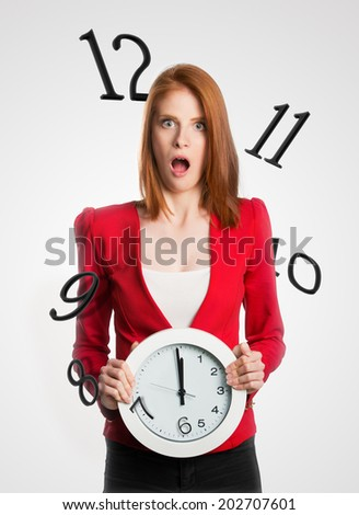 Woman holding a clock with numbers flying away  - stock photo