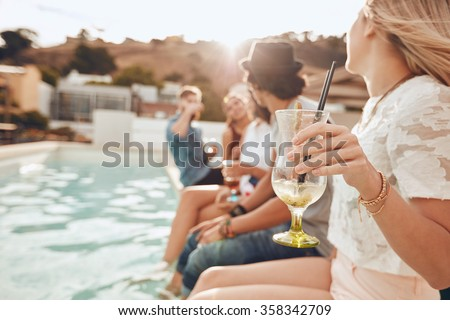 Woman holding a cocktail glass while sitting on the edge of swimming pool with friends. Young people enjoying a poolside party with drinks. Focus on hand and cocktail glass. - stock photo
