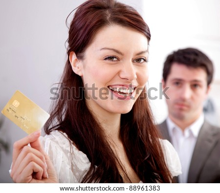 Woman holding a credit card happy with her financial solution - stock photo
