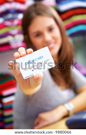 woman holding a credit card in a shop - please note the creditcard numbers are made up - stock photo