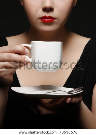 woman holding a cup of black coffee - stock photo