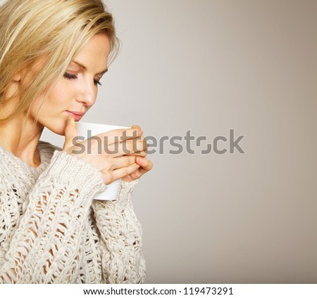 Woman holding a cup of coffee and enjoying the smell of its aroma - stock photo