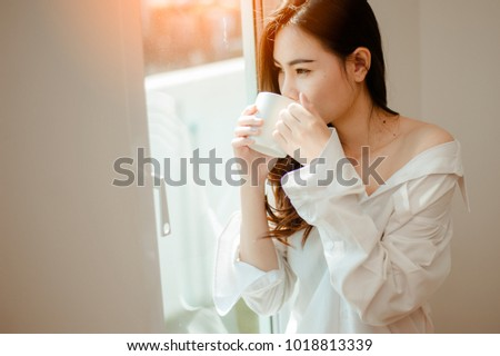 Woman holding a cup of coffee in her hands.Woman drinking coffee at home with sunrise at  window.