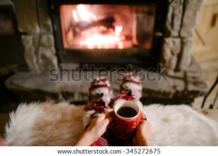 Woman holding a cup of tea by the Christmas fireplace. Woman relaxes by warm fire with a cup of hot drink and warming up her feet in woollen socks. Close up on feet. Winter, Christmas holidays concept - stock photo