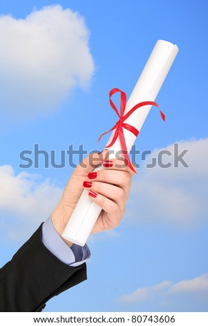 Woman holding a diploma with a red ribbon - stock photo