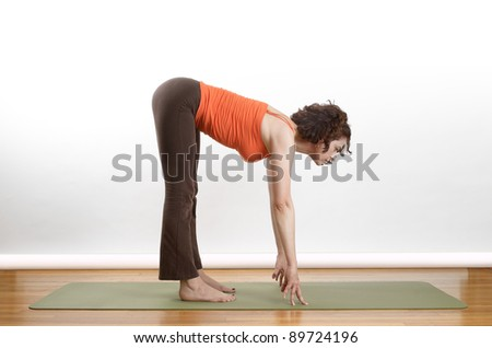 Woman holding a forward bend extension yoga position on a green mat. - stock photo