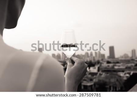 Woman holding a glass of wine while enjoying the city view. - stock photo