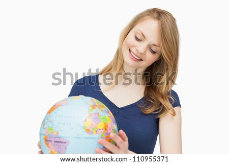 Woman holding a globe while smiling against a white background