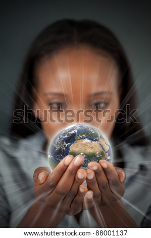 Woman holding a glowing Earth against a dark background - stock photo