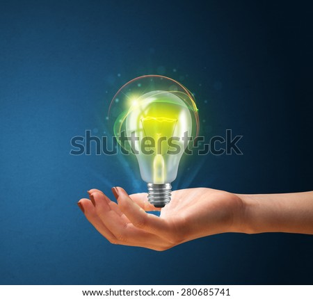 Woman holding a glowing lightbulb in her hand