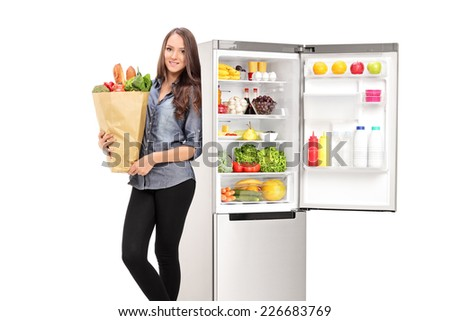 Woman holding a grocery bag by an open fridge isolated on white background - stock photo