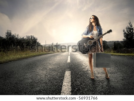 Woman holding a guitar standing on a countryside road - stock photo