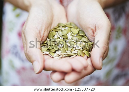 Woman Holding A Handful Of Healthy Seeds - stock photo