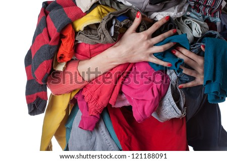Woman holding a huge pile of clothes - stock photo