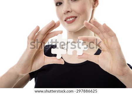 woman holding a jigsaw pieces in her hand shot in the studio - stock photo