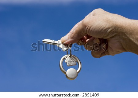 Woman holding a key for a house on a keychain - stock photo