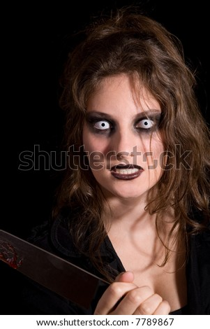 Woman holding a knife and looking totally insane - stock photo