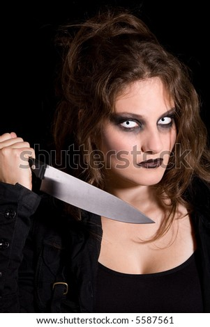 Woman holding a knife as if ready to stab someone with scary eyes - stock photo