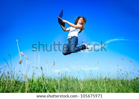 Woman holding a laptop computer jumping over blue sky - stock photo