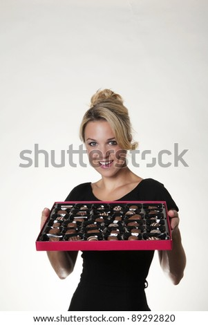 woman holding a large box of chocolates thinking what one to eat next - stock photo
