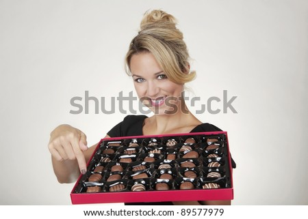 woman holding a large box of chocolates thinking what one to eat next