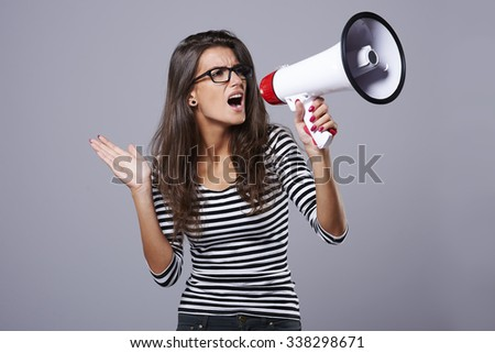 Woman holding a loudspeaker and screaming through it